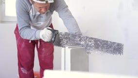 Schoonheids langzame motie in bouw en reparatie - mannelijke tong-en-groefblokken van het bouwers zagende gips stock video