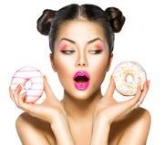 Schoonheids modelmeisje die kleurrijke donuts nemen Stock Afbeeldingen