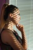 Schoonheids ongerust makende vrouw die in ochtend trog venster en het denken kijkt royalty-vrije stock fotografie