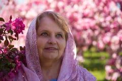 Schoonheids volwassen vrouw die parels dragen onder roze bloemen Stock Fotografie