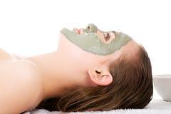 Schoonheidsbehandeling in kuuroordsalon. Vrouw met gezichtskleimasker. Stock Afbeelding