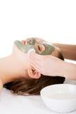 Schoonheidsbehandeling in kuuroordsalon. Vrouw met gezichtskleimasker. Stock Afbeeldingen