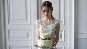 Schoonheidsbruid in bruids toga met cake en kantsluier binnen stock videobeelden
