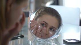Schoonheidsdame die gelflarden zetten onder ogen, die de jeugd en schoonheid van huid houden stock footage