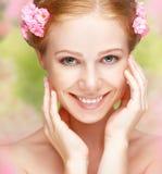 Schoonheidsgezicht van jonge gelukkige mooie vrouw met roze binnen bloemen stock foto