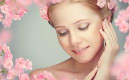 Schoonheidsgezicht van jonge mooie vrouw met roze bloemen Stock Afbeeldingen