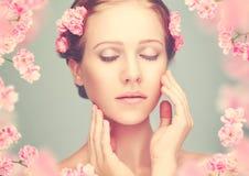 Schoonheidsgezicht van jonge mooie vrouw met roze bloemen stock foto's