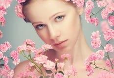 Schoonheidsgezicht van jonge mooie vrouw met roze bloemen stock foto