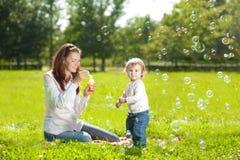 Schoonheidsmamma en baby in openlucht Het gelukkige familie spelen in aard Mo Stock Fotografie