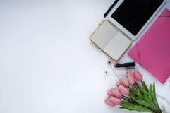 Schoonheidsmateriaal Make-upachtergrond Aspecten van make-up Omslag, tablet, tulpenbloemen, hoofdtelefoons, lippenstift en geslot stock afbeeldingen