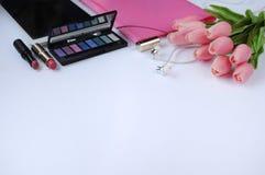Schoonheidsmateriaal Make-upachtergrond Aspecten van make-up Omslag, tablet, tulpenbloemen, hoofdtelefoons, lippenstiften en oogs royalty-vrije stock fotografie