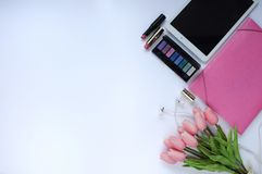 Schoonheidsmateriaal Make-upachtergrond Aspecten van make-up Omslag, tablet, tulpenbloemen, hoofdtelefoons, lippenstiften en oogs stock afbeelding