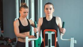 Schoonheidsmeisje die gewichtsoefeningen met hulp van haar persoonlijke trainer doen bij gymnastiek stock footage