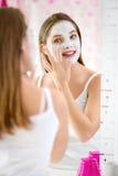 Schoonheidsmeisje die gezichtsmasker krijgen royalty-vrije stock afbeelding