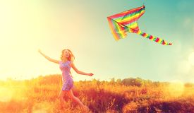 Schoonheidsmeisje die met vliegende kleurrijke vlieger lopen stock afbeeldingen