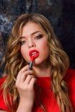 Schoonheidsmeisje die rode Lippenstift toepassen Royalty-vrije Stock Afbeelding