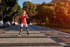 Schoonheidsmeisje rol-schaatst in het stad-park in de warme sunshiny de zomerdag royalty-vrije stock afbeelding