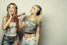 Schoonheidsmeisjes met een en microfoon die zingen dansen Stock Foto's
