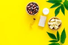 Schoonheidsmiddelen met cacaoboter voor huidzorg Cacaobonen en cacaoboter in kom, zeep, room, olie of lotion in klein stock foto