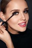 Schoonheidsmiddelen Mooie Vrouw die met Perfecte Make-up Mascara toepassen stock foto