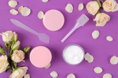 Schoonheidsmiddelen voor gezicht en lichaam in roze flessen met verse rozen op een heldere purpere achtergrond Kuuroord Hoogste m royalty-vrije stock afbeeldingen