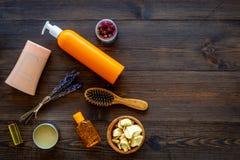 Schoonheidsmiddelen voor haarverzorging met jojoba, argan of kokosnotenolie Flessen en stukken van olie op donkere houten hoogste stock foto