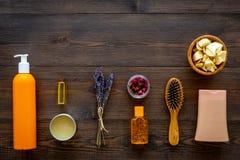 Schoonheidsmiddelen voor haarverzorging met jojoba, argan of kokosnotenolie Flessen en stukken van olie op donkere houten hoogste royalty-vrije stock afbeelding