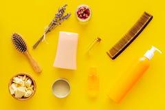 Schoonheidsmiddelen voor haarverzorging met jojoba, argan of kokosnotenolie Flessen en stukken van olie op gele hoogste mening al royalty-vrije stock foto