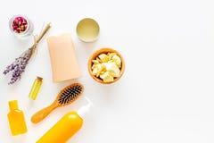 Schoonheidsmiddelen voor haarverzorging met jojoba, argan of kokosnotenolie Flessen en stukken van olie op wit achtergrond hoogst royalty-vrije stock fotografie