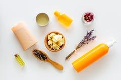 Schoonheidsmiddelen voor haarverzorging met jojoba, argan of kokosnotenolie Flessen en stukken van olie op witte hoogste mening a stock foto