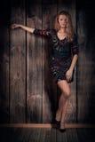 Schoonheidsmodel in korte kleding en hoog-hielschoenen over houten muurachtergrond Stock Foto's