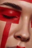 Schoonheidsmodel met rode geschilderde Meetkunde op Gezicht stock afbeelding