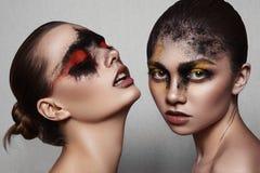 Schoonheidsmodellen met kunstmake-up op glanzende Huid royalty-vrije stock afbeelding