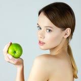 Schoonheidsportret die van jonge vrouw groene appel houden stock foto