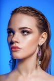 Schoonheidsportret van jong blonde vrouwelijk die model op blauw wordt geïsoleerd stock fotografie
