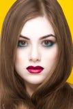 Schoonheidsportret van jong wit meisje met creatieve die make-up en haar op gele achtergrond wordt geïsoleerd Stock Afbeeldingen
