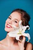 Schoonheidsportret van jonge, aantrekkelijke vrouw met de leliebloem op blauw Stock Foto's