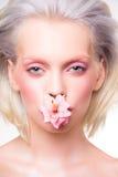 Schoonheidsportret van model met bloem in haar mond Stock Foto