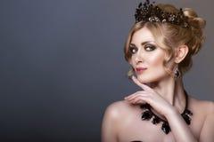Schoonheidsportret van schitterend jong blond model die zwarte juweelkroon en reeks luxueuze halsband en oorringen dragen royalty-vrije stock fotografie