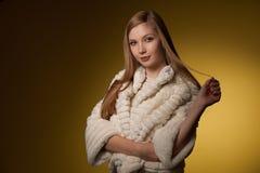 Schoonheidsportret van vrouw in het jasje van de bontwinter over gele backgr Stock Fotografie