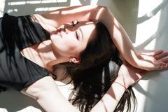 Schoonheidsportret van vrouwelijk gezicht met natuurlijke huid, vrouw die op witte zonnige achtergrond in zwart ondergoed leggen stock fotografie