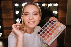 Schoonheidsruimte De vrolijke aardige jonge vrouw kijkt op camera en glimlach Zij die oogschaduw met borstel toepassen Kleurrijk  stock afbeelding