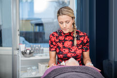 Schoonheidsspecialist Applying Face Cream aan Klant in Salon stock foto's