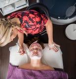 Schoonheidsspecialist Applying Facial Mask aan Vrouw in Salon stock afbeeldingen