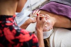 Schoonheidsspecialist Applying Facial Mask op het Gezicht van de Vrouw royalty-vrije stock afbeelding