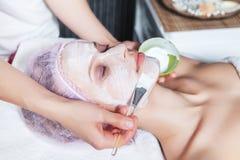 Schoonheidsspecialist die gezichtsmasker toepast op het gezicht stock afbeelding