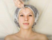 Schoonheidsspecialist die het gezicht van een jonge vrouwelijke cliënt onderzoeken bij kuuroordsalon gezicht het schoonmaken, Una Royalty-vrije Stock Foto's