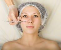 Schoonheidsspecialist die het gezicht van een jonge vrouwelijke cliënt onderzoeken bij kuuroordsalon gezicht het schoonmaken, Una Royalty-vrije Stock Fotografie