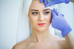Schoonheidsspecialist die jonge vrouwen` s wenkbrauwen in kuuroordcentrum in de was zetten stock afbeeldingen