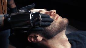 Schoonheidsspecialist die massage op mensen` s gezicht doen bij de salon van de kapperswinkel stock video
